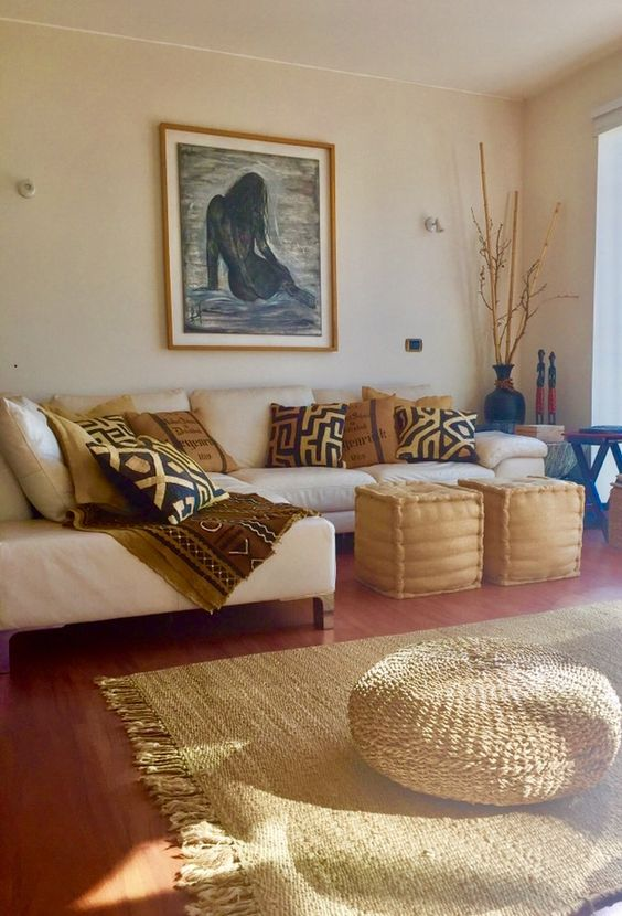 living room, wooden floor, rug, rattan ottoman, white sofa, brown ottoman, pillows with tribal pattern