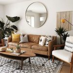 Living Room, Wooden Floor, White Rug, Brown Leather Sofa, Wooden Chairs With White Cushion, Wooden Long Round Coffee Table, Round Mirror On The White Wall, Plants