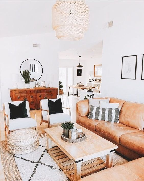 living room, wooden floor, wooden coffee table, rattan rug, white fur rug, white chair, brown leather corner sofa, brown wooden cabinet, round mirror, rattan covered chandelier