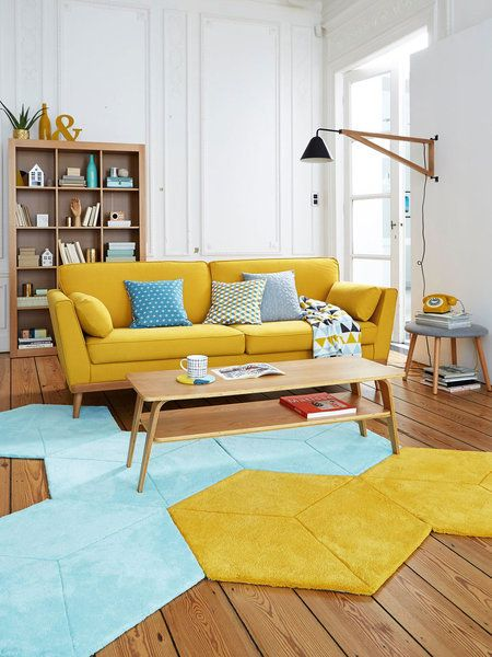 living room, wooden floor, yellow blue geometric rug, yellow sofa, white wall, wooden shelves, wall lamp, wooden coffee table, wooden stool