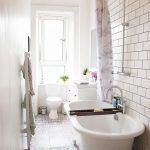 Long And Narrow Bathroom With Patterned Tiles On Floor, White Tile On Wall, Round Curtain Cail, White Tub, White Toilet, White Cabinet And Mirro