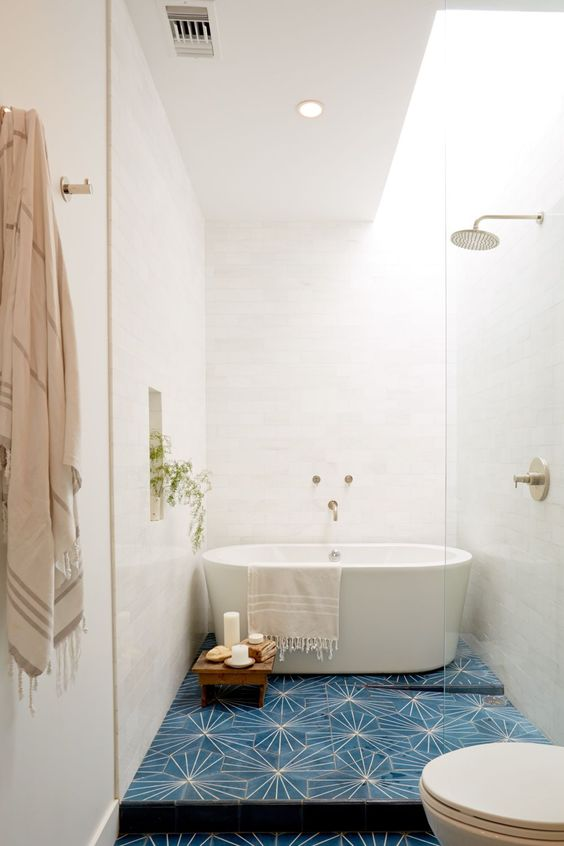 long bathroom with blue floor, whtie wall, whtie toilet, white bathtub, golden faucet and shower, glass partition