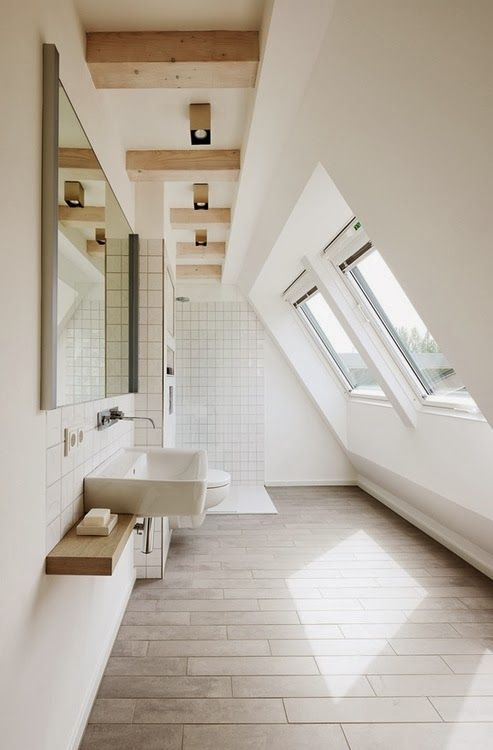 long bathroom with slope ceiling, wooden floor tiles, white walls, white wall tiles, glass windows on slope ceiling, mirror, white toilet, white sink,
