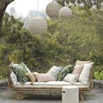 Long Chair With Hight Arm Rest From Light Brown Rattan Material With White Cushion, Pastel Colored Pillows