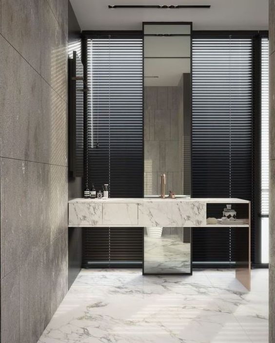 long tall mirror from the ceiling to the floor in a bathroom with marble vanity and sink, marble floor, tiles wall
