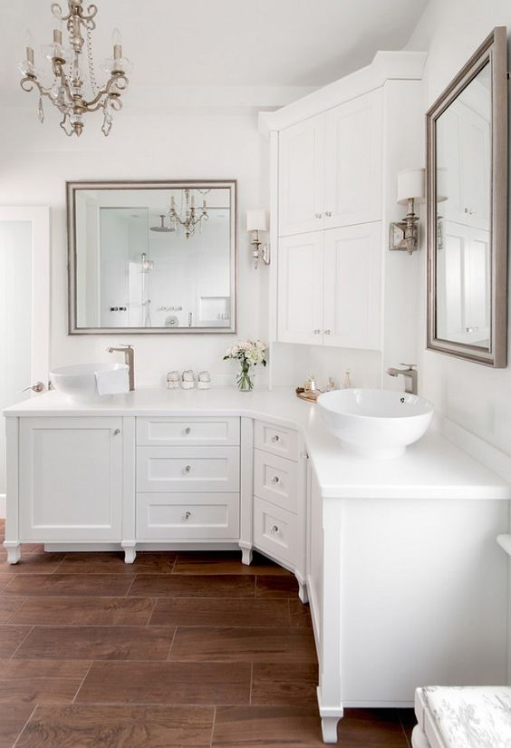 long white corner vanity with cabinet with drawers, white bowl sink, white cabinet above, large square mirrors