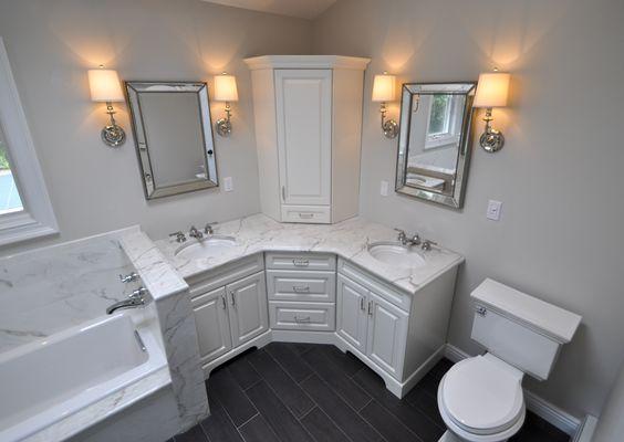 medium sized corner vanity with white marble sink, white cabinet, cornerd top cabinet, two mirrors