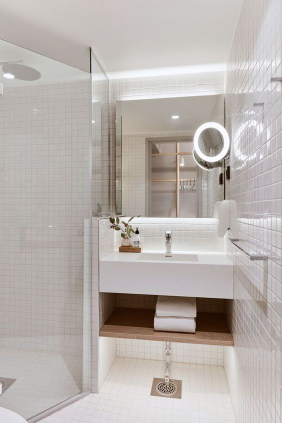 mirror in the bathroom that is square, with added mirror with ring of lights as frame