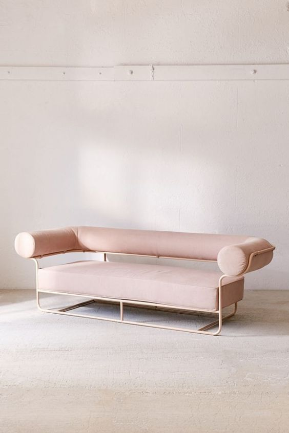 muted pink sofa with thin metal support, round long back and arm rest