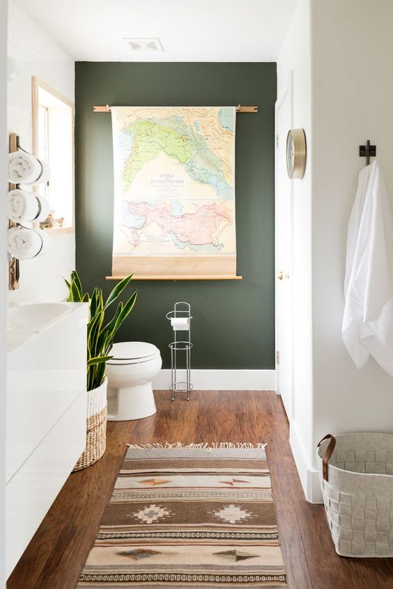 narrow bathroom with wooden floor, white wall, white sink, deep sage green accent wall