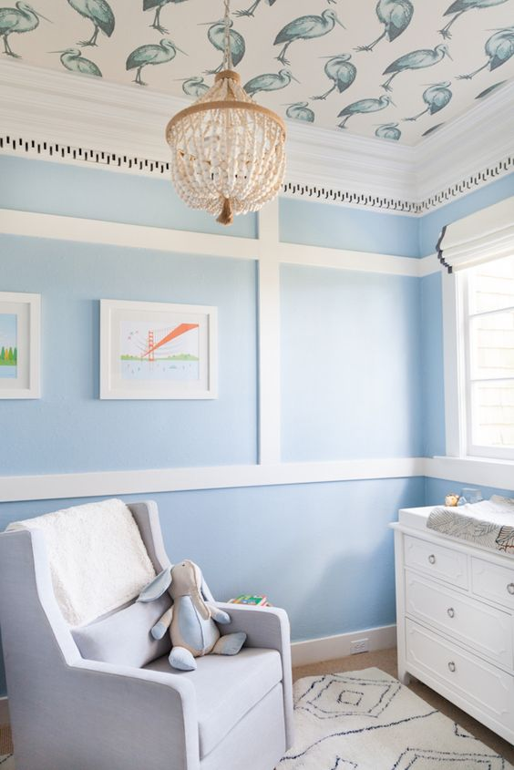 nursery with wooden floor, rug, chair, baby changing station, blue wall, ceiling with birds picture, chandelier