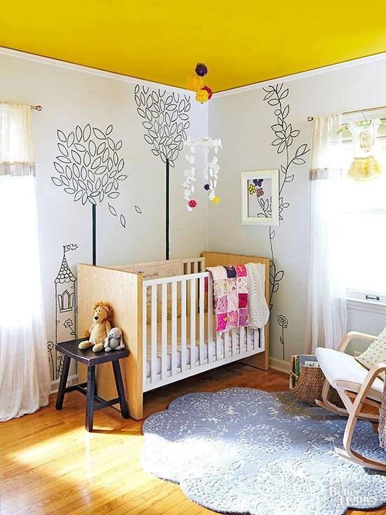 nursery with wooden floor, wooden cribs, white wall with some wallpaper, wooden rocking chair, blue rug, yellow painted ceiling