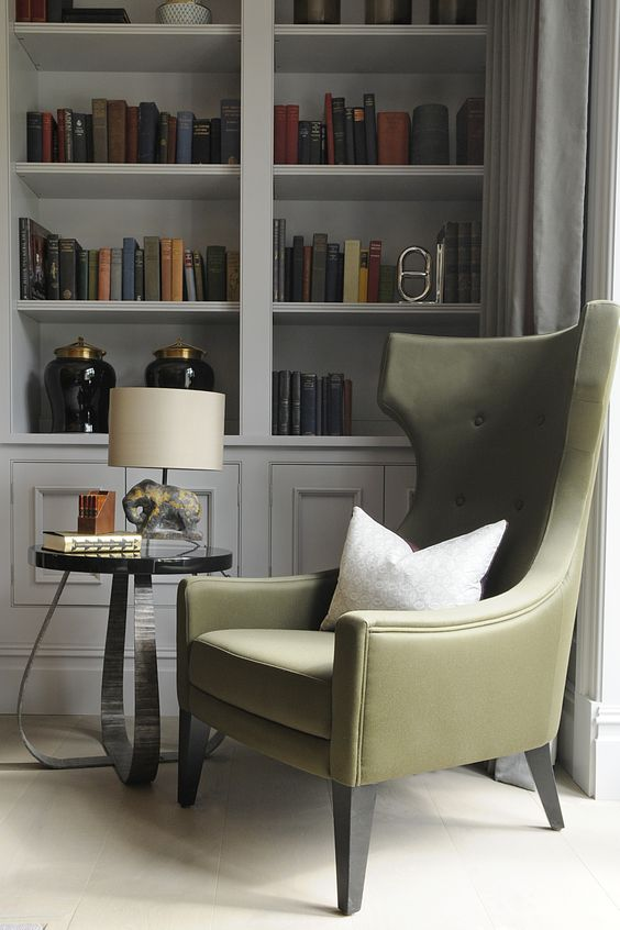 olive green chair with round side table, table lamp, white wooden shelves, near the window