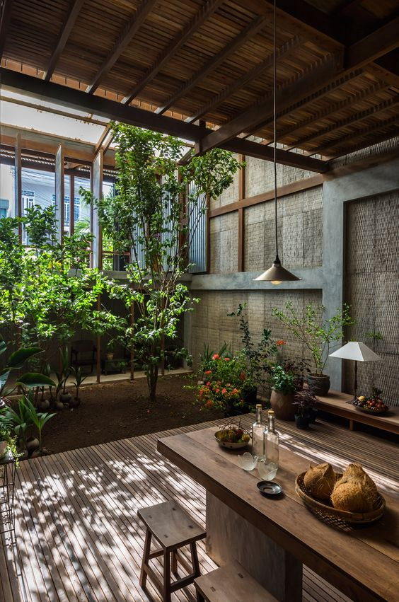open dining area with wooden floor, wooden table, wooden stools, plants outside