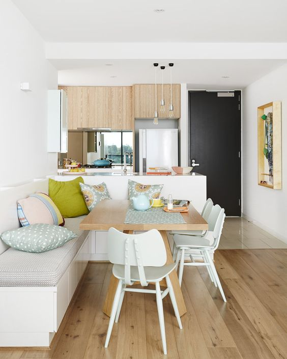 open room with kitchen with wooden cabinet, wooden floor, corner dining room with white bench, wooden table, white chairs