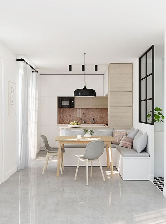 open room with white marble floor, white wooden cabinet with marble backsplash, white bench with thin grey cushion, wooden table