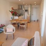 Open Room With Wooden Floor, Grey Sofa, Beige Chair, Wooden Dining Set, Metalic Kitchen