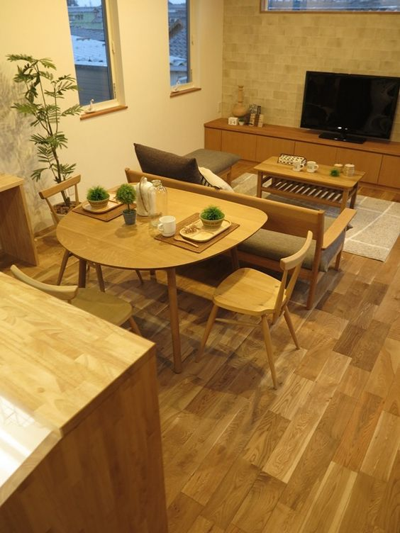 open room with wooden floor, wooden table, wooden sofa with grey cushion, wooden dining set, wooden countertop, wooden cabinet under tv