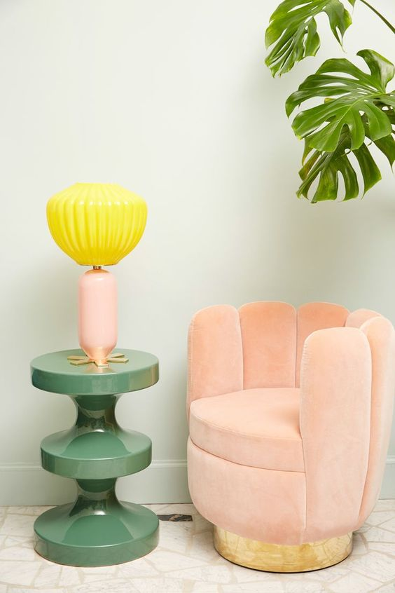 pink small low chair shpaed like opened shells near green table with yellow shells lamp