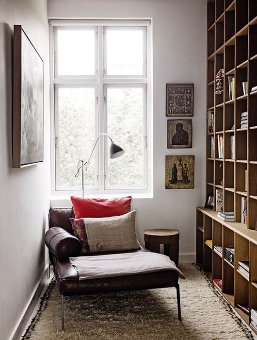 reading corner in an alcove with rug, wooden shelves, leather lounge chair with wooden stool, floor lamp, near the window