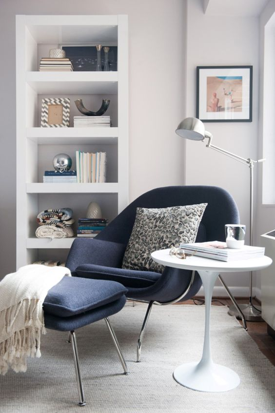 reading corner with white round table, rug, dark blue chair with ottoman, shite shelves, silver floor lamp, near the windows