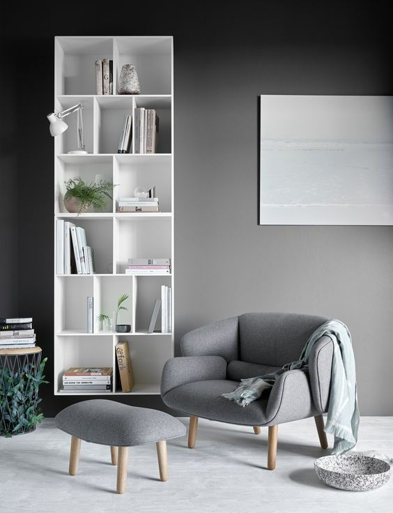 reading nook with grey floor, grey modern chair with ottoman, white shelves, grey wall