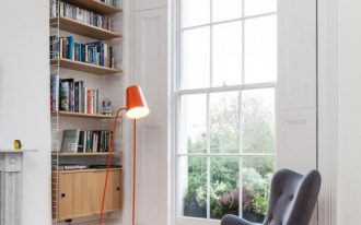 reading nook with wooden floor, white wall, floating shelves in the alcove, grey chair with ottoman, orange floor lamp, near the window