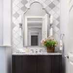 Room With Wooden Floor, Dark Colored Wooden Cabinet, Grey Marble Vanity, Grey Arabesque Accent Wall, Mirror, White Sconces