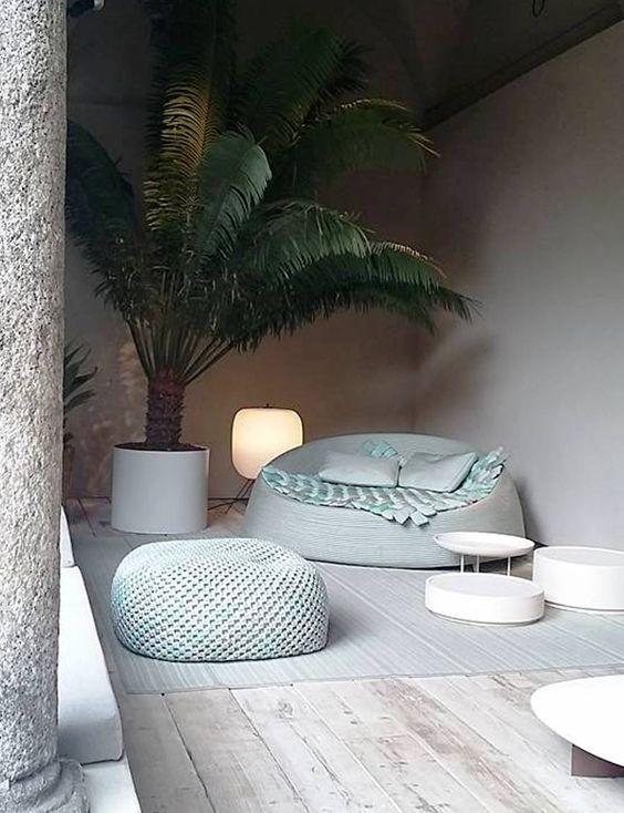 round green sofa with blanket, green pillows, green ottoman, white round coffee table