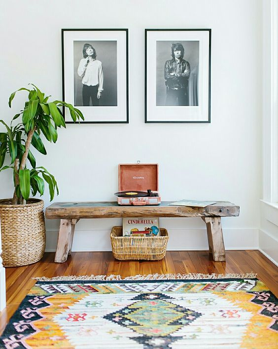 rustic basic wooden bench on entry hall with white wall, wooden floor, plants on woven pot, rattan basket, rug