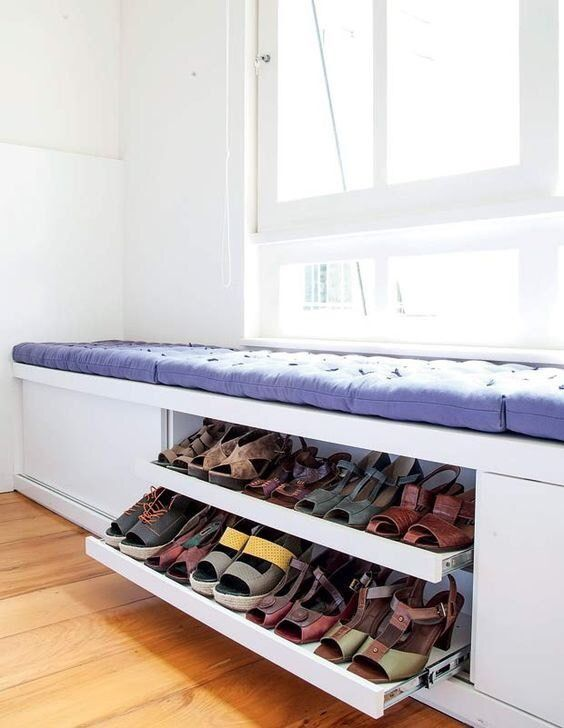 shoe storage under the bench of white wood with purple cushion