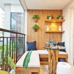 Small Balcony With White Tiles, White Walls With Wooden Accent Wall, Pots On The Wall, On The Floating Shelves, Wooden Bench With White Thin Cushion, Wooden Table With Glass Top