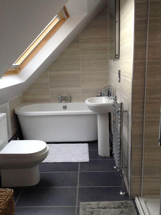 small bathroom, grey tiles, brown wall tiles, white toilet, white tub, white sink, metal rack, mirror, mat, glass window