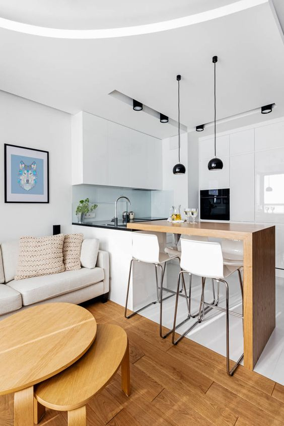 small kitchen open room with living room with dark glass kitchen top, white cainet on top, wooden island for dining area with white stool