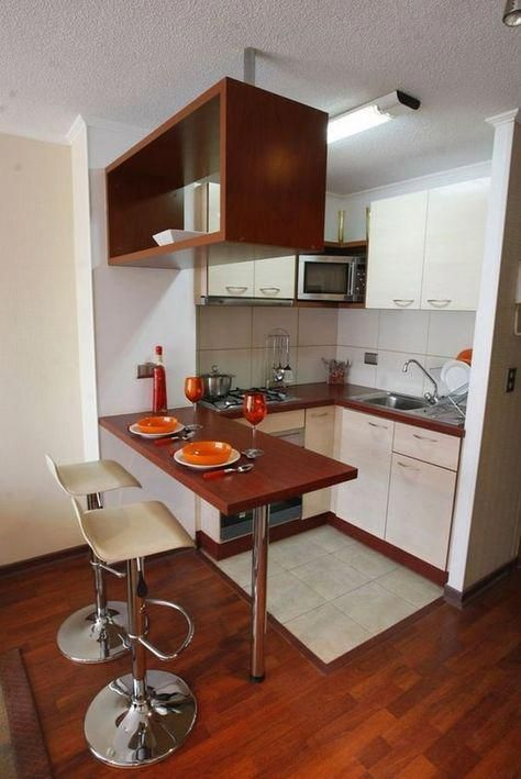 small kitchen with white and brown cabinet, brown bar, white stool,