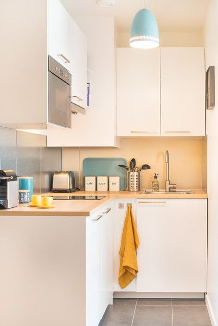 small kitchen with white cabinet under and on top, brown wooden kitchen top, brown backsplash, blue pendant, grey floor