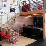 Small Loft, Dark Floor, Rug, Living Room Under Bedroom Level, Wooden Stairs, Shelves On Stairs, Red Chairs, Ottoman,