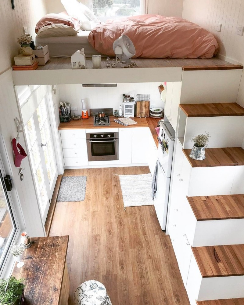 small loft, wooden floor, white stairs with shelves, kitchen under, glass door, glass window, bedroom on top with glass window