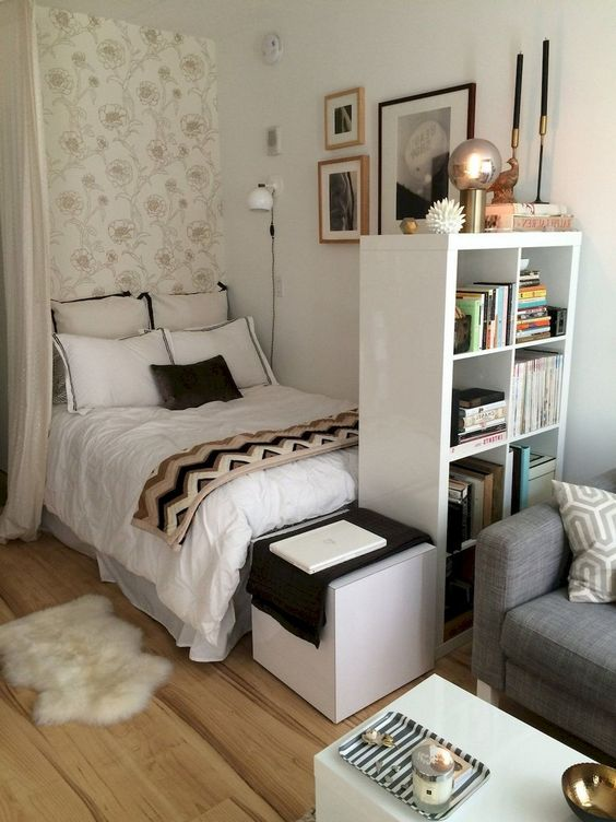 studio apartment bedroom with wooden floor, white walls, accent wall, white bookshelves, grey sofa, white square table, coffee table