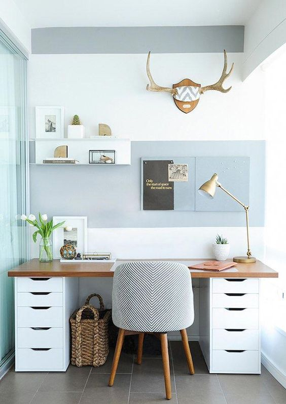 study area with gry floor, white wall, glass wall, white brown table, grey chair, blue painted area with boards and shelves, table lamp