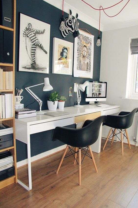 study area with wooden floor, dark wall, wite table, black modern midcentury chair, shelves on the side, white table lamp, wall pictures