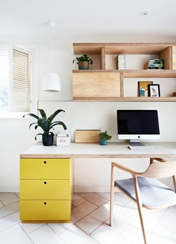 study room with white wall, white patterned floor, white table with yellow cabinet, wooden chair, wooden shelves above