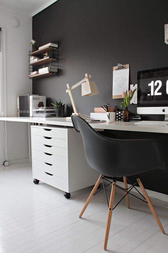 study room with white wooden floor, white table, black modern midcentury chair, black wall, shelves, white cabinet, table lamp