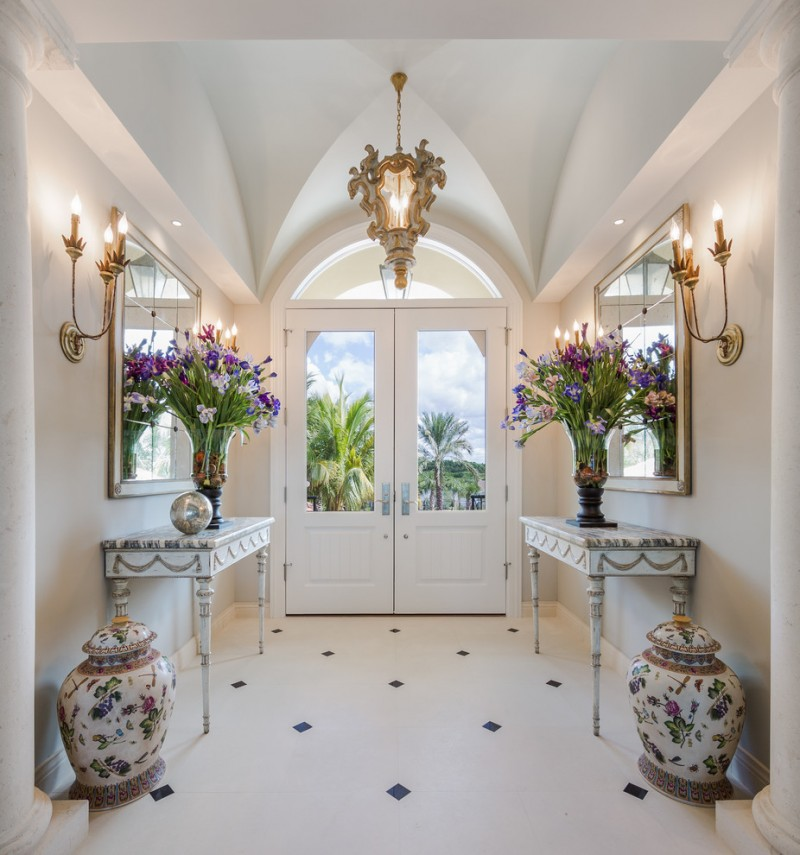 table for entry way antique tables wall mirrors wall sconces glass window white glass double front doors floor tile flower vase chandelier
