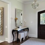 Table For Entry Way Black Table Wall Mirror Chandelier Dark Brown Wooden And Glass Door Area Rug White Stools Table Lamp Candle Purple Walls