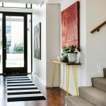 Table For Entry Way Pink Artwork Black Framed Glass Doors Slim Table Yellow Legs Stairs Black And White Rug Flower Pots Windows Brown Floor