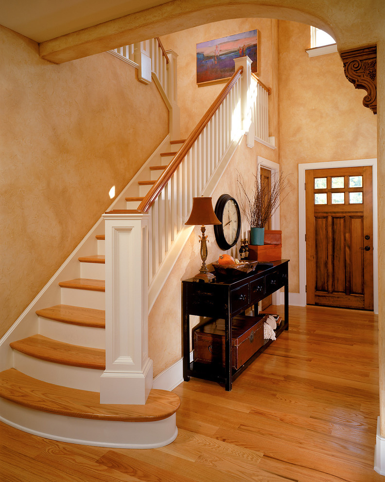 table for entry way staircase wooden floor black table drawers trunk brown table lamp wooden doors clock beige walls tray stair railing