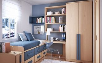 teen bedroom with wooden floor, cupboard, table and shelves, platform bed with drawers in brown and blue, blue accent wall,