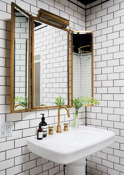 three golden framed mirrors with two side angled, lamp on top of the mirrrors