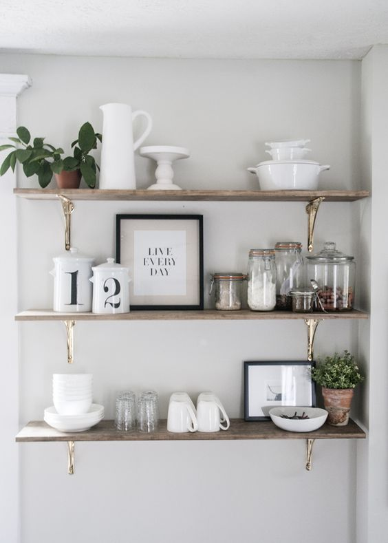 three lines of open shelves with golden support against white painted wall, brown wooden shelves, kitchen utensils, ingredients, and tea set